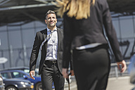 Smiling businessman with luggage at car park looking at woman - MADF000947