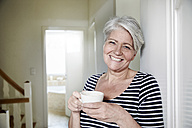Portrait of smiling woman with cup of coffee at home - FMKF002724