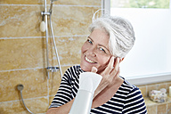 Portrait of smiling woman blow-drying her hair - FMKF002730