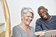 Portrait of laughing man and woman with digital tablet - FMKF002733