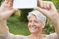 Portrait of smiling woman taking selfie with smartphone - FMKF002736