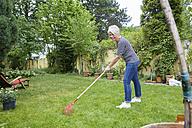 Woman raking on meadow in the garden - FMKF002745