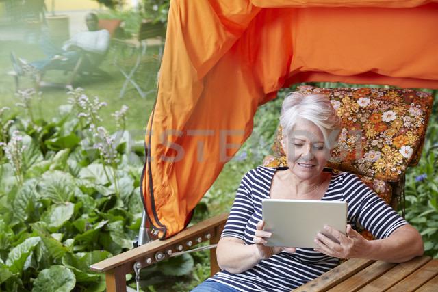 Woman sitting in lawn chair using digital tablet - FMKF002748
