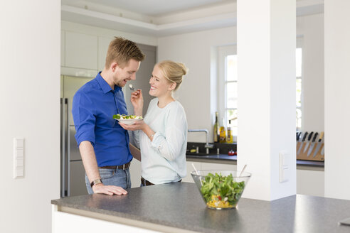 Happy couple in kitchen with salad - SHKF000607