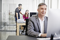 Mature businessman and coworkers working in office - RHF001495
