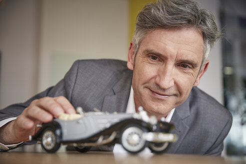Mature man playing with classic car model - RHF001555