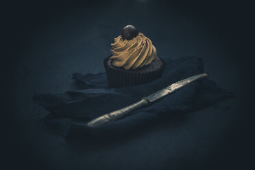 Cupcake with chocolate cream in front of dark background - ASCF000604