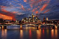 Germany, Frankfurt, view to skyline with Ignatz-Bubis-Bridge and Main River in the foreground by sunset - RUEF001724