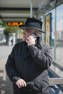 UK, Bristol, senior man telephoning with smartphone while waiting at bus stop - JCF000009