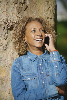 Portrait of smiling woman wearing denim shirt telephoning with smartphone - JCF000016