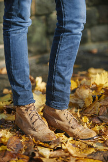 Woman wearing leather boots, standing on autumn leaves, partial view - JCF000019