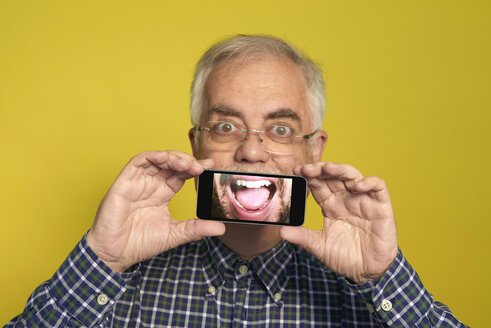 Portrait of senior man holding smartphone with photography of open mouth - JCF000032