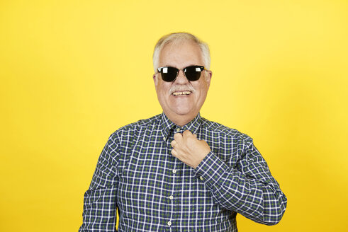 Portrait of smiling senior man wearing sunglasses in front of yellow background - JCF000038