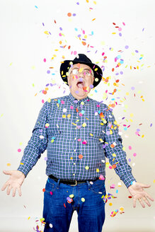 Portrait of senior man watching falling confetti - JCF000041