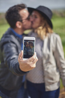 Selfie of kissing couple on display of smartphone - JCF000047