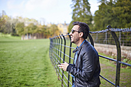 Laughing man with smartphone wearing leather jacket and sunglasses - JCF000050
