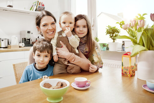 Portrait of happy mother with her three little children in the kitchen - MFF002971