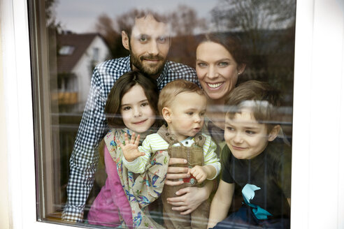 Happy family of five looking through window pane - MFF002974