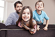 Portrait of grinning little girl at home with father and brother in the background - MFF002977