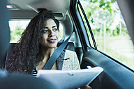 Smiling young woman in car with folder - UUF007477