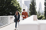 Young man and woman with cell phone and document outdoors - UUF007486