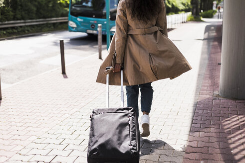 Young woman with luggage at bus stop - UUF007513