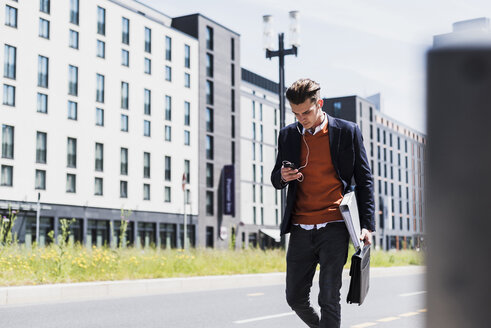 Young man with cell phone and earbuds on the move - UUF007525