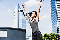 Enthusiastic young woman raising her arms outdoors - UUF007558