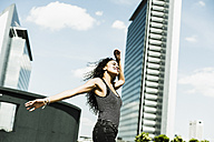 Enthusiastic young woman with outstretched arms outdoors - UUF007561