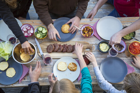 Family eating burgers at beer table - SARF002727