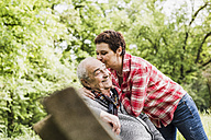 Happy woman kissing her old father sitting on a bench in nature - UUF007571