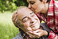 Portrait of happy senior man kissed by his daughter - UUF007574