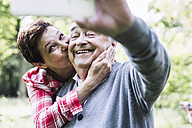 Happy senior man taking selfie with his daughter - UUF007580