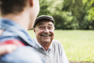 Portrait of senior man talking with his grandson - UUF007595