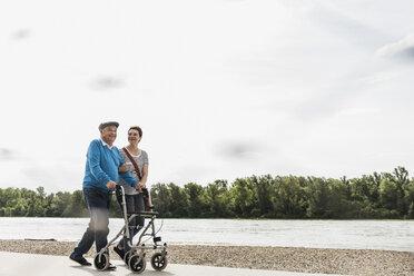 Senior man strolling with his daughter at riverside - UUF007607