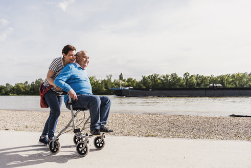 Woman pushing her old father sitting on wheeled walker - UUF007619