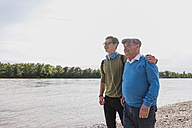 Grandfather and grandson standing at riverside looking together at distance - UUF007631