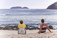 Indonesia, Sumbawa island, Two young men sitting at the beach - KNTF000304