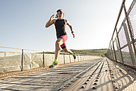 Athlete running and jumping on a bridge - JASF000729