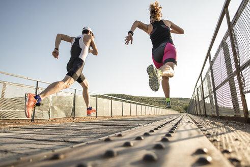 Two athletes running on a bridge - JASF000732