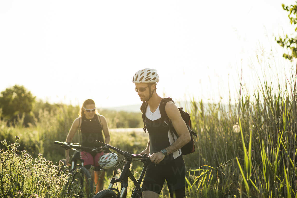 Two athletes pushing bicycles in rural landscape - JASF000738 - Jaen Stock/Westend61