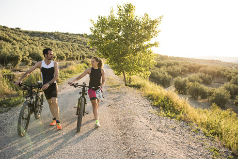Sportive man and woman pushing bicycles and talking in rural landscape - JASF000744