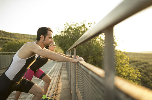 Sportive man and woman stretching on a bridge at sunset - JASF000747
