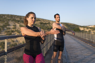 Sportive man and woman stretching on a bridge - JASF000750