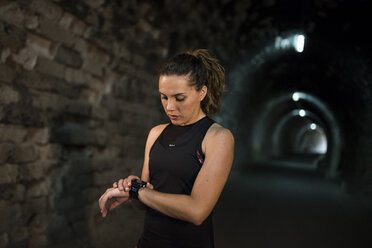 Sportive woman looking at smartwatch in a tunnel - JASF000753