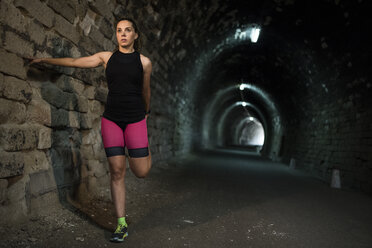 Sportive woman stretching in a tunnel - JASF000756