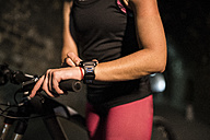 Sportive woman with bicycle using smartwatch in a tunnel - JASF000759
