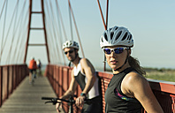 Sportive man and woman with bicycles resting on a bridge - JASF000762