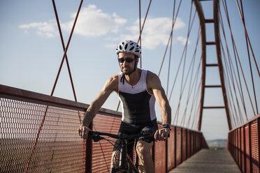 Athlete riding bicycle on a bridge - JASF000765