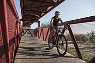 Athlete riding bicycle on a bridge - JASF000768